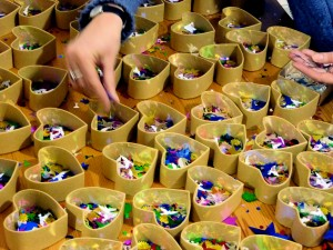 Produktion: Herz-Schachteln werden mit Glitzerfiguren gefüllt.